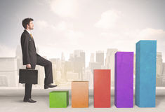 Business person climbing up on colourful chart pillars concept Royalty Free Stock Images