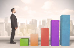 Business person climbing up on colourful chart pillars concept Royalty Free Stock Photography