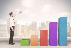 Business person climbing up on colourful chart pillars concept Royalty Free Stock Photos