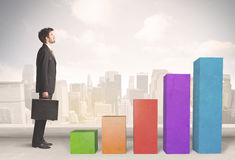 Business person climbing up on colourful chart pillars concept Stock Image