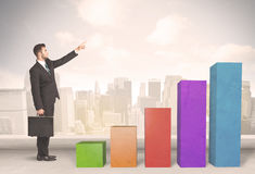 Business person climbing up on colourful chart pillars concept. On city background Stock Images