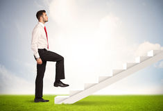 Business person climbing up on white staircase in nature Royalty Free Stock Photos