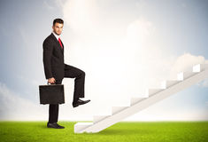Business person climbing up on white staircase in nature Stock Photos