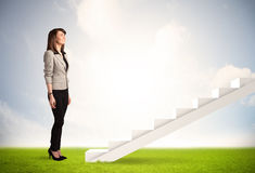 Business person climbing up on white staircase in nature Stock Photo