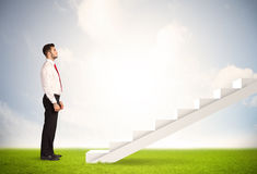 Business person climbing up on white staircase in nature Stock Images