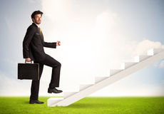 Business person climbing up on white staircase in nature Royalty Free Stock Image