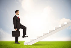 Business person climbing up on white staircase in nature Royalty Free Stock Images