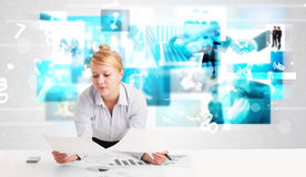 Business person at desk with modern tech images at background Royalty Free Stock Image