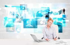 Business person at desk with modern tech images at background Stock Image