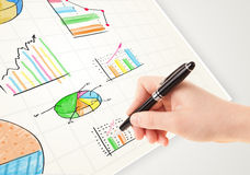 Business person drawing colorful graphs and icons on paper Royalty Free Stock Photos