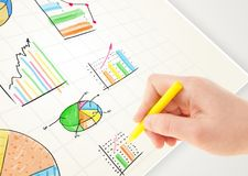 Business person drawing colorful graphs and icons on paper. Business person drawing colorful graphs and icons on plain paper Royalty Free Stock Images
