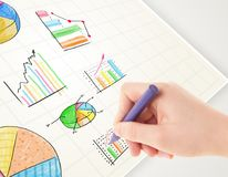Business person drawing colorful graphs and icons on paper. Business person drawing colorful graphs and icons on plain paper Royalty Free Stock Photo