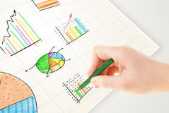 Business person drawing colorful graphs and icons on paper Stock Images