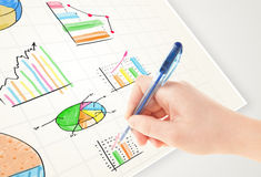 Business person drawing colorful graphs and icons on paper Stock Photo