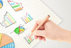Business person drawing colorful graphs and icons on paper Stock Image