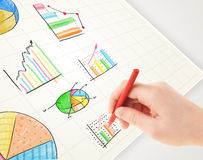 Business person drawing colorful graphs and icons on paper Royalty Free Stock Photo