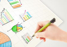Business person drawing colorful graphs and icons on paper Stock Photos
