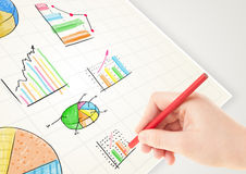 Business person drawing colorful graphs and icons on paper. Business person drawing colorful graphs and icons on plain paper Stock Photo
