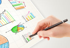 Business person drawing colorful graphs and icons on paper Royalty Free Stock Image