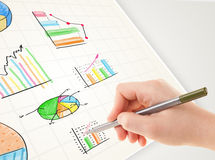 Business person drawing colorful graphs and icons on paper Royalty Free Stock Photography