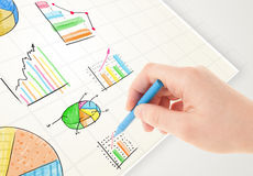 Business person drawing colorful graphs and icons on paper. Business person drawing colorful graphs and icons on plain paper Stock Photography