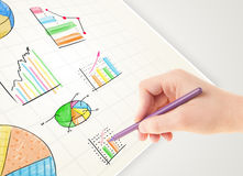 Business person drawing colorful graphs and icons on paper. Business person drawing colorful graphs and icons on plain paper Stock Images