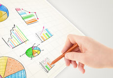 Business person drawing colorful graphs and icons on paper. Business person drawing colorful graphs and icons on plain paper Royalty Free Stock Photos