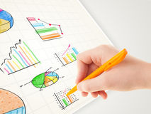 Business person drawing colorful graphs and icons on paper Royalty Free Stock Images