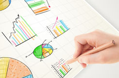 Business person drawing colorful graphs and icons on paper. Business person drawing colorful graphs and icons on plain paper Stock Image