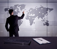 Business person drawing dots on world map. A young office worker drawing on world map and connecting dots with lines, presenting marketing sterategy at office Royalty Free Stock Photos