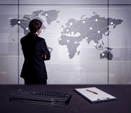 Business person drawing dots on world map. A young office worker drawing on world map and connecting dots with lines, presenting marketing sterategy at office Royalty Free Stock Images