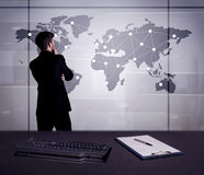 Business person drawing dots on world map. A young office worker drawing on world map and connecting dots with lines, presenting marketing sterategy at office Stock Images