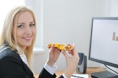 Business person eating at computer Stock Photo