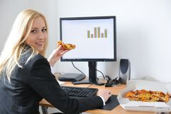 Business person eating pizza at computer stock image