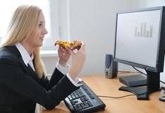 Business person eating pizza at work royalty free stock image