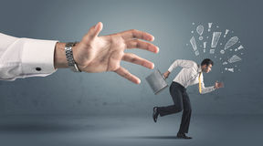Business person getting away from a big hand Royalty Free Stock Images