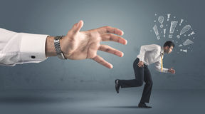 Business person getting away from a big hand Stock Images