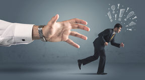 Business person getting away from a big hand Royalty Free Stock Image