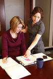Business person help. A young woman helps her coworker with a business project royalty free stock images