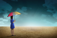 Business Person Hold Umbrella On Desert. Business person holding umbrella standing on the desert Stock Photo