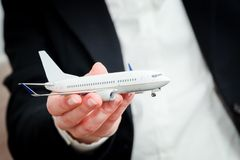 Business person holding airplane model. Transport, aircraft industry, airline. A business person holding an airplane model in hand. Concepts of aerial transport Stock Photography