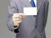 Business person holding a blank name card. Businessman in suit holding a blank name card, gray background Royalty Free Stock Photos
