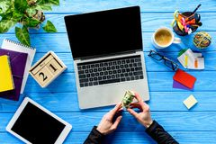 Business person holding dollars by laptop on blue wooden table royalty free stock images