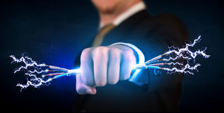 Business person holding electrical powered wires Royalty Free Stock Photography