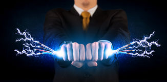 Business person holding electrical powered wires Stock Photos