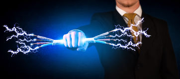 Business person holding electrical powered wires Royalty Free Stock Images