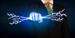 Business person holding electrical powered wires Stock Photography