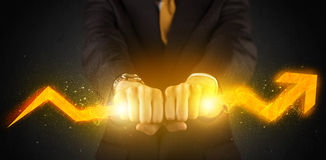 Business person holding a hot glowing upright arrow Stock Photo