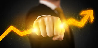 Business person holding a hot glowing upright arrow Royalty Free Stock Photography