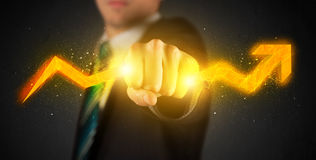 Business person holding a hot glowing upright arrow Royalty Free Stock Photo
